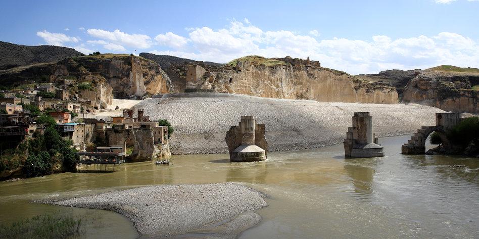 Die alte Stadt Hasankeyf am Tigris mit einer alten Brücke und historischen Bauten erstrahlt in der Abenddämmerung.
