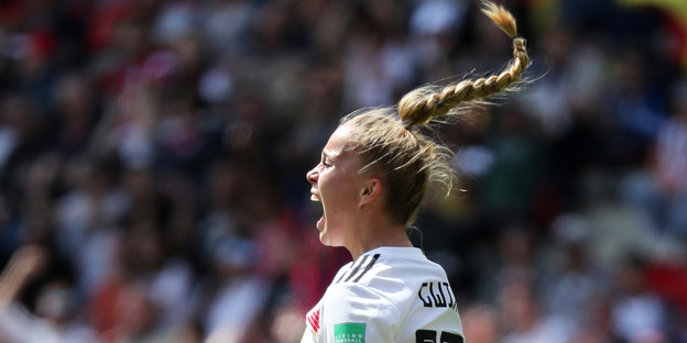 EIne Fußballerin jubelt. Ihr geflochtener Zopf fliegt in die Höhe.