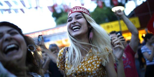 Zwei Frauen in der Menge von Menschen, sie lachen und feiern den Sieg ihres KAndidaten Ekrem Imamoglu