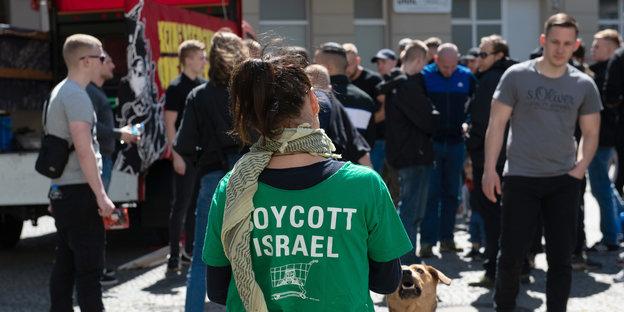 """Eien frau trägt ein """"Boykott Israel""""-Shirt, im Hintergund mänliche Mitglieder des Jugendwiderstands"""