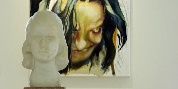 Die Büste einer Frau steht vor einem Porträtgemälde