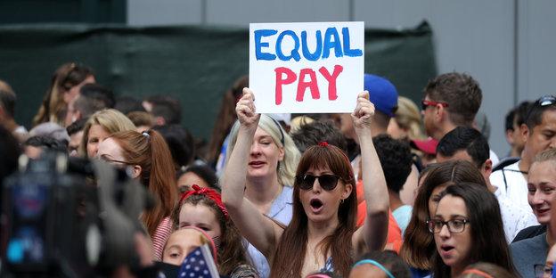 An der Parade für das Fußballteam steht eine Frau mit einem Schild, auf dem