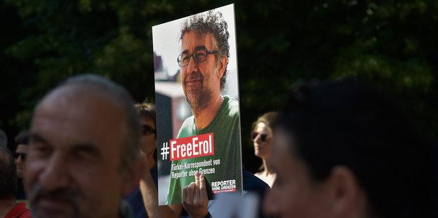menschen halten ein Plakat, auf dem #FreeErol steht und das gesicht von Erol Önderoglu abgebildet ist