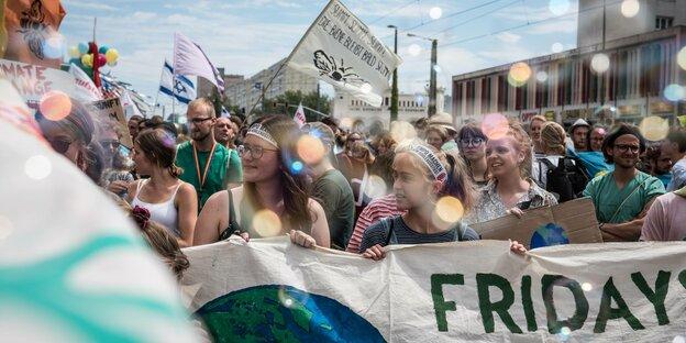 """Schülerinnen halten ein Banner mit der Aufschrift """"Fridays for Future"""" dahinter zahlreiche Fahnen"""