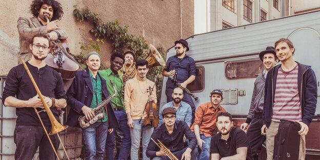 Dreizehn Männer mit Instrumenten stehen auf einem Hinterhof: Banda Comunale.