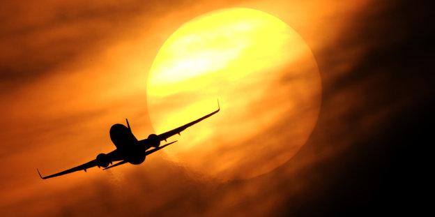 Ein Flugzeug startet am Flughafen in Düsseldorf vor der untergehenden Sonne.