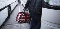A person enters a bus with a british flagged bag