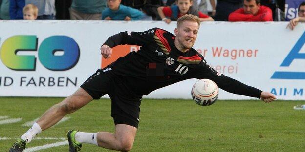 Abwehrspieler Sebastian Thomas versucht mit einem Hechtsprung den Ball zu erreichenhech