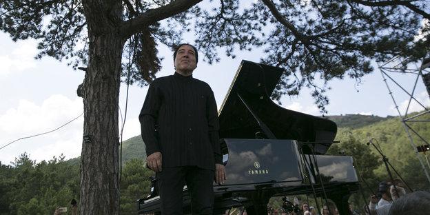 Mann mit Klavier unter einem Baum