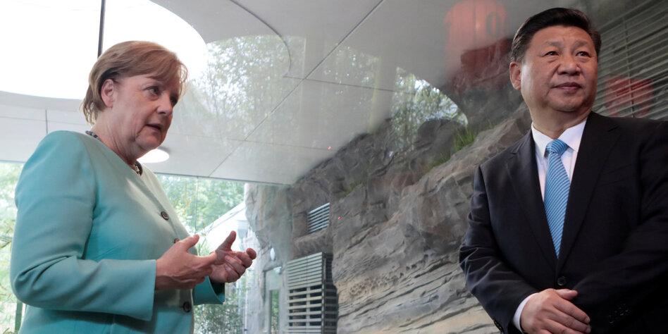 Merkel gestikultiert in Richtung Xi Xi schaut in die andere Richtung