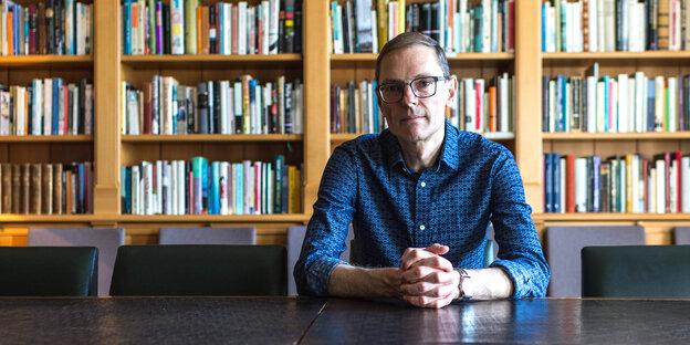 Ein Mann sitzt vor einer Bücherwand. Es ist Martin Puchner