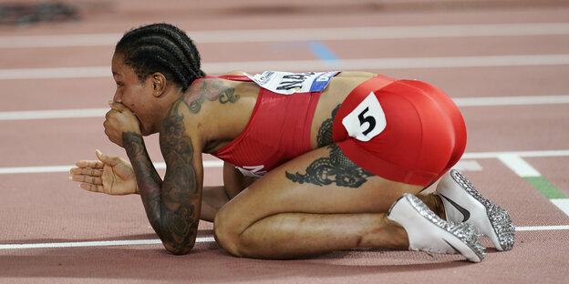 Athletin hält sich die Hand vor den Mund und hockt auf der Bahn