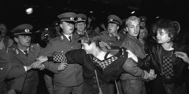 Eine Frau versucht eine Demonstrantin von einer Polizeikette weg zu ziehen