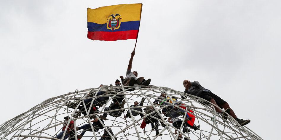 Demonstranten hießen die Flagge Ecuadors auf einer Skulptur