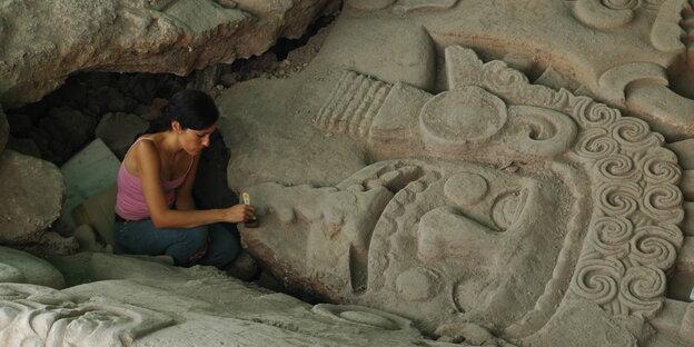 Eine Archäologin bei der Freilegung der monolithischen Stein in Mexiko-Stadtskulptur der Göttin Tlaltecuhtli