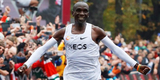 Eliud Kipchoge breitet die Arme aus, während er jubelnd ins Ziel läuft