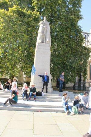 ein Mann steht vor einem Denkmal mit einer Fahne