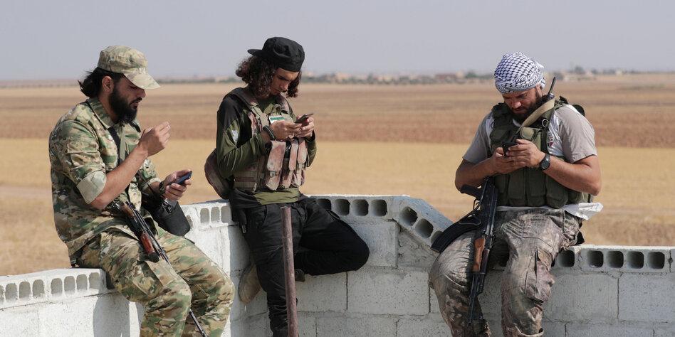 Drei Kämpfer mit Waffen sitzen auf einer Mauer und schauen in ihre Smartphones.
