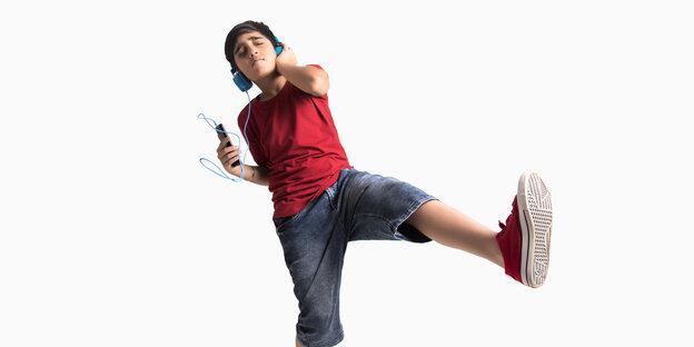 Ein Junge tanzt mit Kopfhörern vor neutralem Hintergrund.