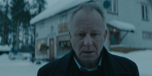 Ein Mann im Schnee vor einem Haus.