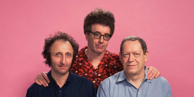 Drei Männer vor rosa Hintergrund