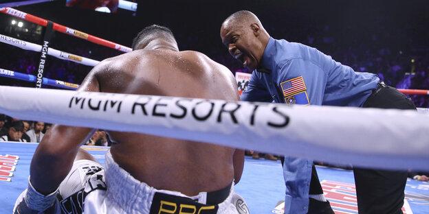 ein Boxer sitzt in der Ringecke auf dem Boden und wird von Schiedsrichter angezählt