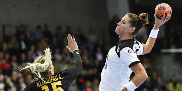 Eine Handballerin in einem weißen Trikot beim Wurf