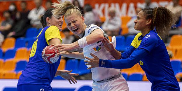 Zwei brasilianische Handballerinnen versuchen Kim Naidzinavicius aufzuhalten