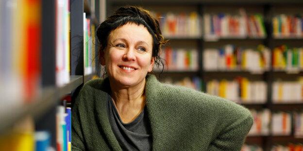 Olga Tokarczuk in einer Bibliothek, sie lehnt sich an ein Ragl an und lächelt wach in die Kamera
