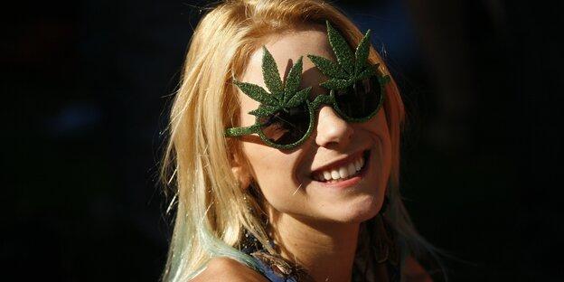 Junge Frau mit einer Sonnebrille in Hanfblätterform