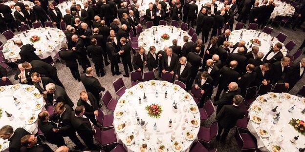 Beim Fest der Bremer Eiswette stehen schwarz gekleidete Männer um runde Tische