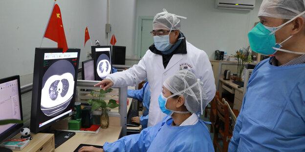 Trois médecins avec des protège-dents examinent une tomographie par ordinateur