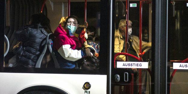 Les gens avec des masques sont assis dans un bus