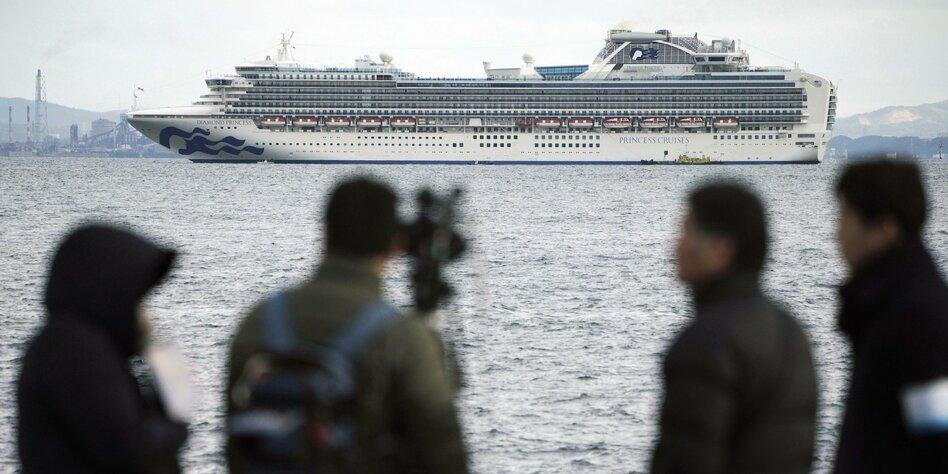 Im Hintergrund ein Kreuzfahrtschiff im Vordergrund die Rücken einiger Personen unscharf