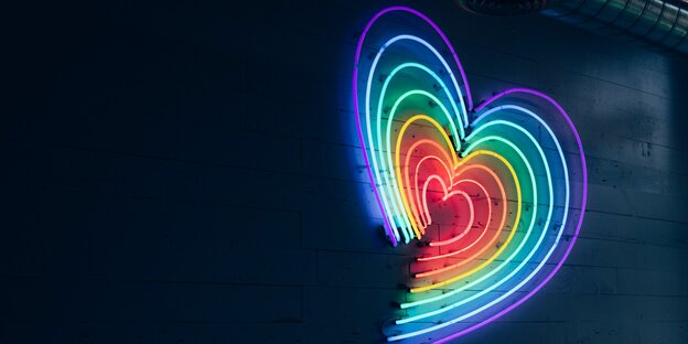 Ein regenbogenfarbenes Herz leuchtet an einer Wand