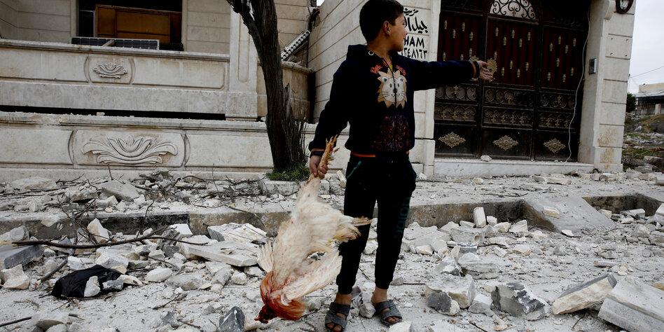 Ein Junge mit einem toten Huhn in der Hand steht auf einer mit Schutt übersäten Straße