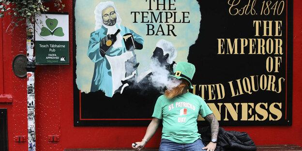 Un homme est assis seul devant un pub à Dublin.