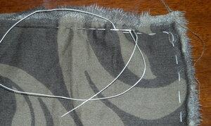 Ein Stück Stoff, am Rand ist eine Naht, Nadel und Faden sind zu sehen