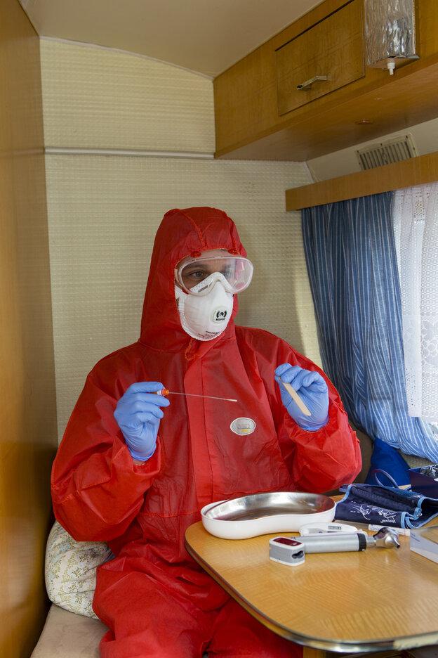 Man in red protective suit in a caravan
