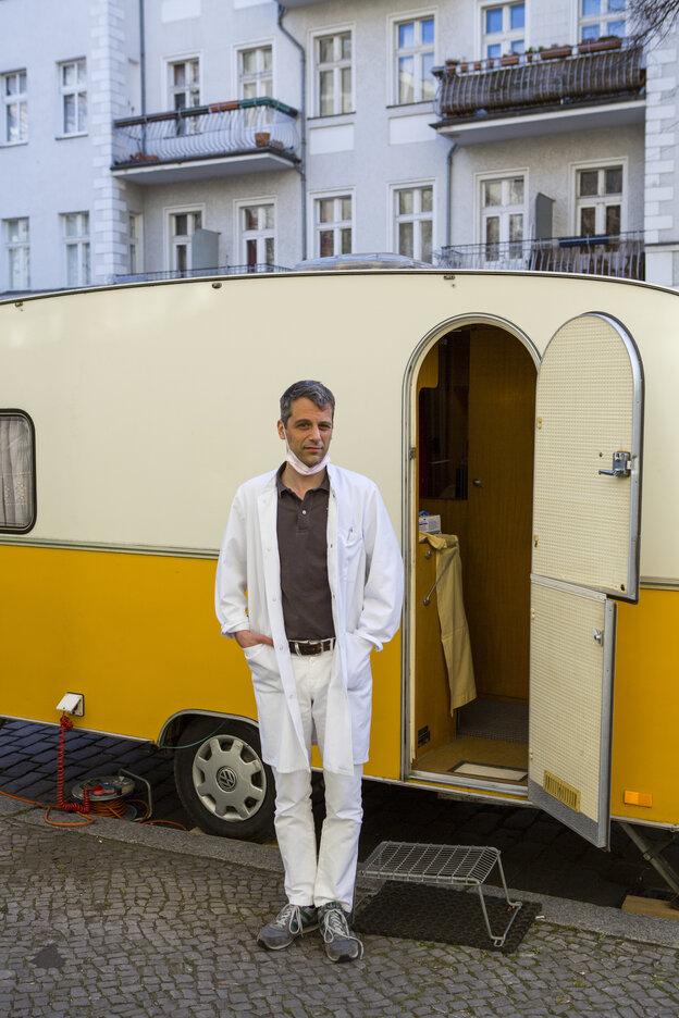 Man in doctor's smock in front of a caravan
