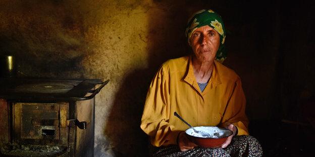 Eine ältere Frau sitzt neben einem Herd und hält einen Teller in der Hand