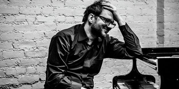 Ein Mann mit Brille sitzt lächelnd am Klavier.