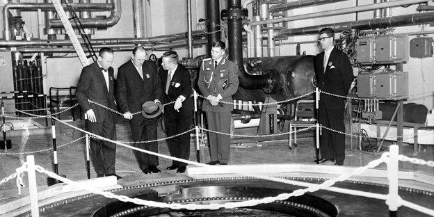 Ein altes schwarz-weiß Foto, auf dem Alte Männer um einen Reaktor stehen