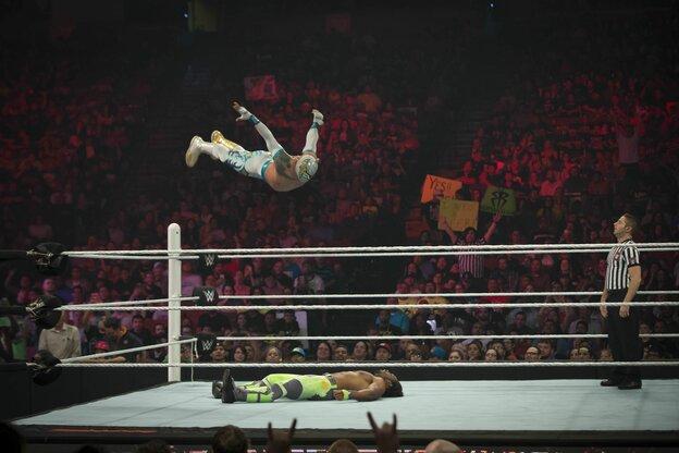 Zwei Wrestler im Ring. Einer macht einen Diving Headbutt, er springt von oben mit ausgebreiteten Armen auf seinen am Rücken liegenden Gegner