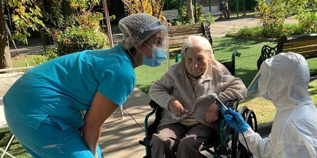 An old woman in a wheelchair with two nurses.