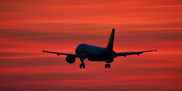 An airplane against a red sky.