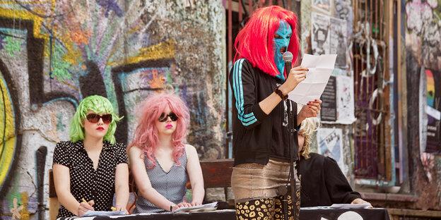 Frauen mit grellen Perücken demonstrieren