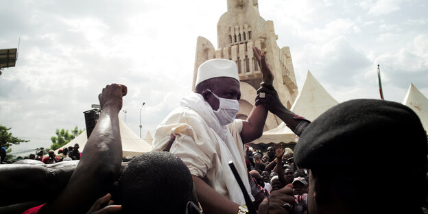 Imam Mahmoud Dicko in Mitten einer Menschenmenge. Er ragt über die Köpfe der andren empor und hebt seinen arm. Jemand berührt seine Hand. Dicko trägt eine Maske.