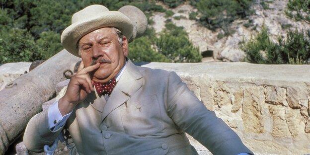 Mann mit Hut und hellem Anzug