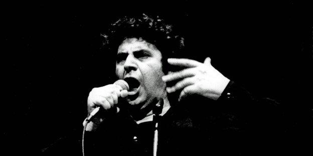 Schwarzweißes Foto, dunkler Hintergrund, ein Mann mit vollen Locken singt ins Mikro.